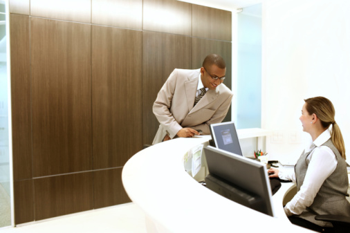 EXECUTIVE TALKING WITH RECEPTIONIST